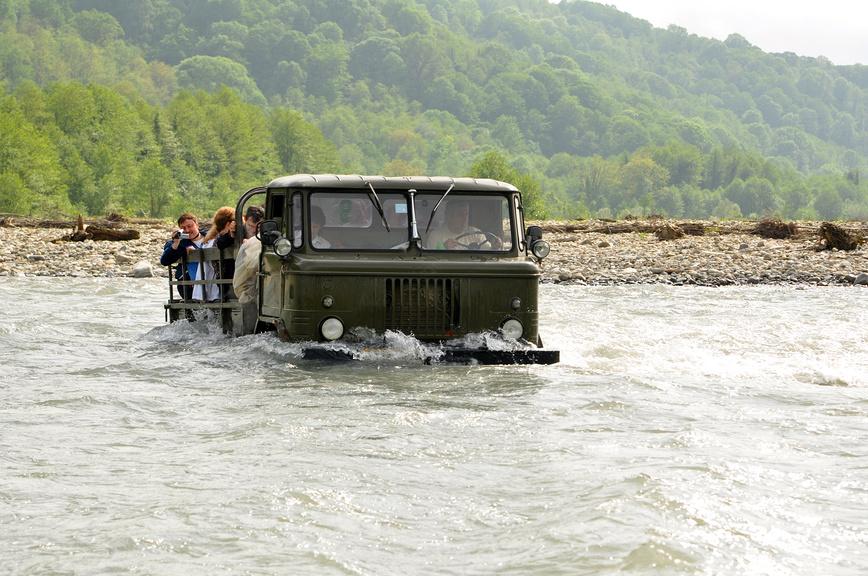 Экскурсанты преодолевают реку Шахе по дороге на 33 водопада